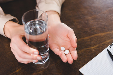 close-up partial view of businesswoman holding pills and glass of water at workplace