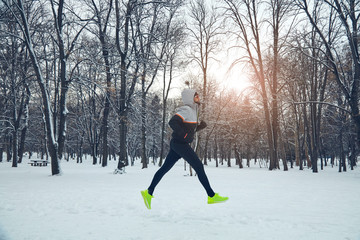 Man jogging in snowy park and cold weather.