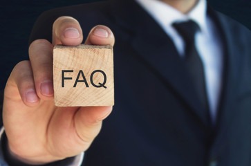 Wall Mural - Man holding FAQ message on wooden cube. Frequently Asked Questions