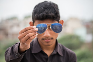 Young man holding sunglasses in front of his eyes
