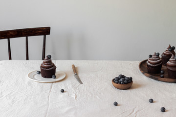 Chocolate muffins with chocolate swirl topping and fresh blueberries on the table