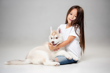 Portrait of a joyful little girl having fun with siberian husky puppy on the floor at studio. The animal, friendship, love, pet, childhood, happiness, dog, lifestyle concept