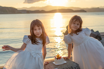 The sunset seaside and two girls and a birthday cake