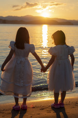 Two girls holding hands with Sunset