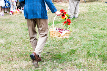 Man back walking, holding Easter blessing basket, flowers, embroided, embroidery towel, people outside church