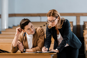female teacher in glasses checking exam results of male student in classroom