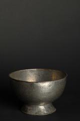 ancient metal bowl on dark background. antique bronze tableware
