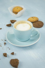 Cup of coffee with cookies on blue background
