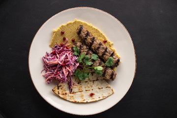 Indian style shish kofta kebab with pickled onion and pita bread on black background