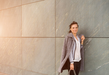 Businesswoman With Long Coat Leaning On Gray Tiled Wall