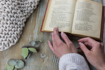 Female hands with open book on wooden background