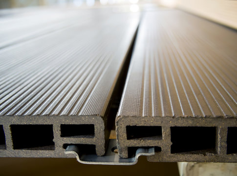 The terrace board from a polymeric composite fastened by a metal collar