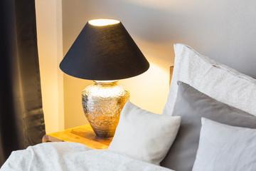 Illuminated Lamp On Table In Bedroom