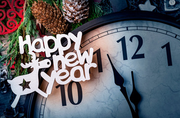 Wall clock in Christmas or New Year decorations are wrapped with fir branches and Christmas decorations. On the clock five minutes to midnight.