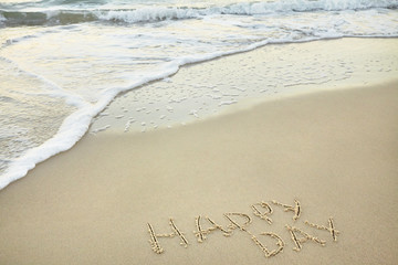 handwritten inscription happy day made in the sand near the water, the wave washes text on the beach