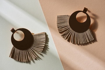top view of beautiful luxury brown earrings on beige and white surface with sunlight