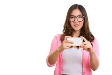 Young happy Asian woman taking picture with mobile phone