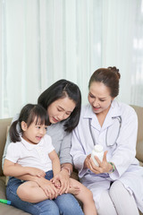 Mature Vietnamese pediatrician prescribing vitamins to little girl