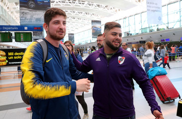 Fans of Boca Juniors and River Plate embrace before their departure to Spain to attend the Copa Libertadores final, at Ezeiza airport in Buenos Aires