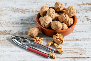 The whole and cracked walnuts on the table.