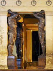 Hermitage with statues of Atlanteans in near the entrance to the historical building at night. Saint Petersburg, Russia