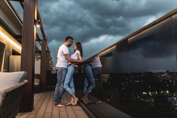 Profile of happy couple standing on balcony and embracing . Copy space on right side. Grey clouds on background