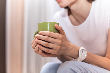 Close up of hands of woman holding cup. Her body is on blurred background. Copy space on left side
