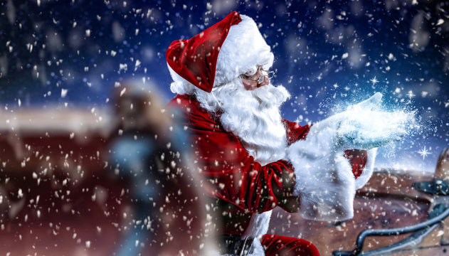 Red old Santa Claus and magic night with snowflakes