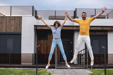 Hilarious couple are holding hands and jumping high. Full length portrait. Copy space on left side