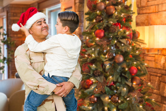 Hispanic Armed Forces Soldier Wearing Santa Hat Hugging Son In Front Christmas Tree