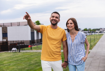 Cheerful man is holding hands with his girlfriend and pointing up. she looking at mentioned direction with smile. Street on blurred background
