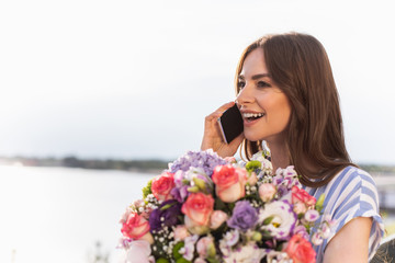Happy woman holding flowers and looking aside with wide smile. She using smartphone for conversation. Copy space on left side