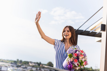 Waist up portrait of cheerful lady holding big bouquet and waving. She looking aside with wide smile. Copy space on left side