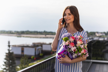Waist up portrait of blithesome girl using smartphone and holding box with various flowers. She looking ahead with smile. Quay on blurred background
