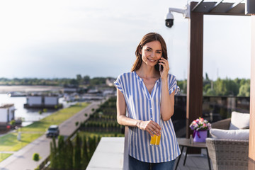 Waist up portrait of young woman standing on balcony and speaking on handy. She looking at camera with smile. Copy space on left side