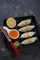 Cast-iron serving pan with fried korean dumplings and dipping sauces, elevated view on a brown stone background