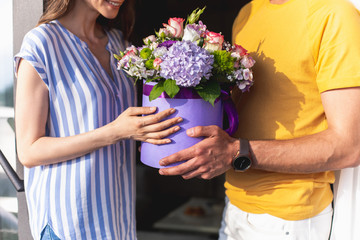 Male person is giving box with flowers to smiling woman. Focus on present