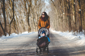 Young beautiful woman with stroller walking in the snowy park on sunny day in winter