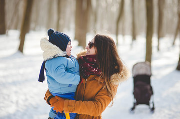 Happy young mother holding her son in her arms while walking in the beautiful snowy park on sunny winter day.
