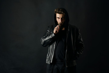 Man with vaping mod exhaling steam at black studio background. Bearded guy smoking e-cigarette to quit tobacco. Vapor and alternative nicotine free smoking concept