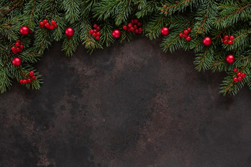 Christmas holiday background with fir-tree branches with red berries and balls. Top view, close up dark concrete background.
