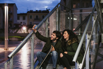 Couple of teenagers take a selfie on an outdoor staircase at sunset in the city