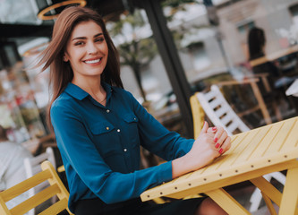 Concept of success and well-being. Waist up side on portrait of smiling beautiful lady in stylish cloth sitting in cozy outdoor cafe. Copy space on right