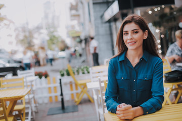 Concept of success and well-being. Waist up portrait of smiling business lady sitting in cozy outdoor cafe. Copy space on left