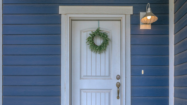 Wreath hanging on the white door of a blue home