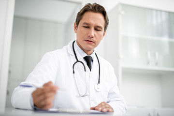 Thoughtful general practitioner looking attentively at the notes on his table and holding a pen