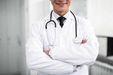 Cheerful enthusiastic doctor with stethoscope on his neck standing with his arms crossed and smiling happily