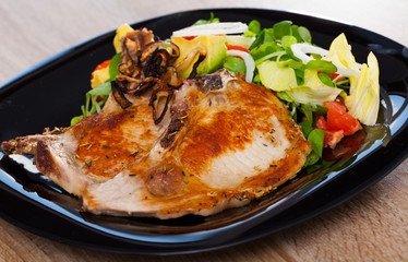 Frying pork loin at plate with salad from avocado, tomatoes and corn salad