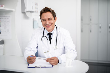 Happy doctor. Positive enthusiastic general practitioner sitting at the table in his clinic and smiling while holding a pen