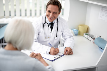 Positive emotional general practitioner sitting with the clipboard on the table and kindly smiling to his patient Wall mural